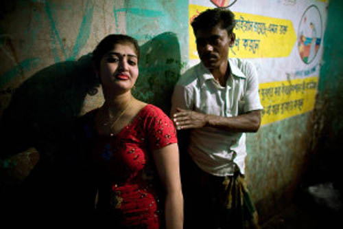 A young chowkri (bonded sex worker) waits for customers on the 3rd floor of the Joinal Bari brothel in Faridpur, central Bangladesh. About 800 women and girls live and work inside the bustling brothel, comprised of four buildings situated on an important trading route on the banks of the Padma river. Many of chowkri are underage. Some of the girls are runaways who leave home to escape a bad situation or marriage, and end up on the brothels when they have no where else to go. Many others have been kidnapped and sold to a madame by a parent or relative. They must take on 5-10 clients per day, and most receive no pay because they must repay their debt to their madame. ..