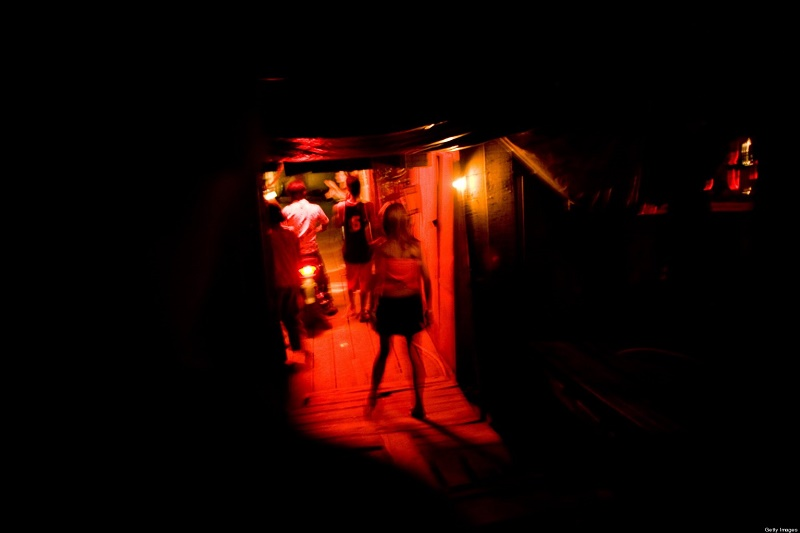 PHNOM PENH, CAMBODIA - MARCH 20:  A prostitute walks into a brothel on March 20, 2007 in Phnom Penh, Cambodia.  (Photo by Jeff Hutchens/Getty Images)
