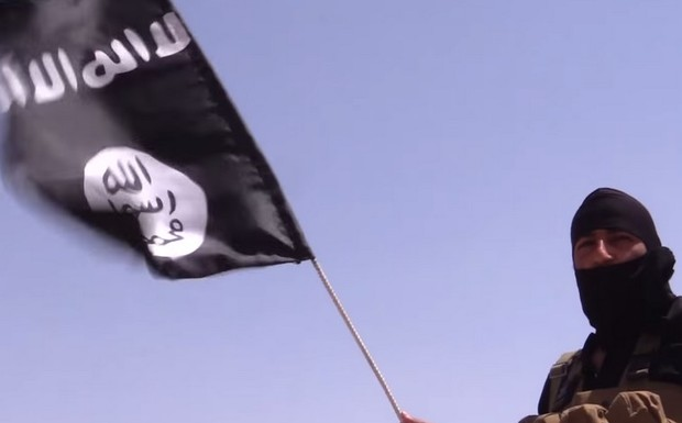 An+Islamic+State+terrorist+holds+a+flag