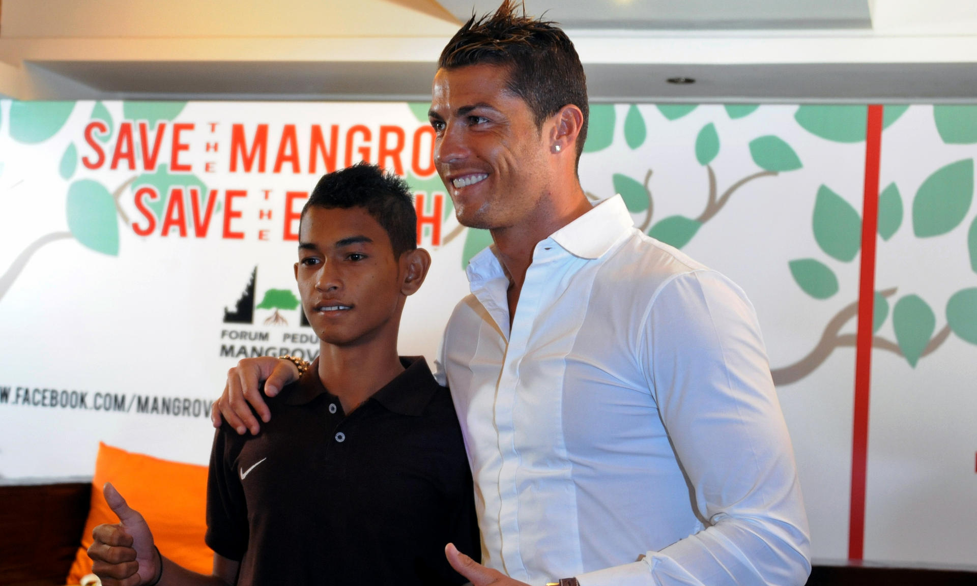 Football player Christiano Ronaldo (R) is reunited with 16-year-old Martunis (L), an Indonesian survivor of the deadly 2004 Aceh tsunami who the Real Madrid star met in 2005 during a mission to assist tsunami victims and gave his family financial assistance. Ronaldo participated in a conservation movement in Indonesia aiming to raise public awareness of the importance of mangrove forests.  AFP PHOTO/SONNY TUMBELAKA