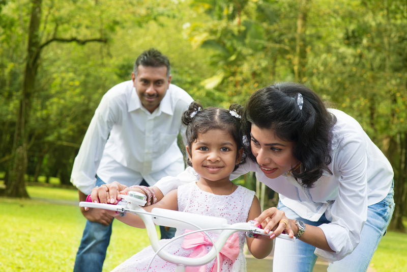 Indian family outdoor activity. Asian parent teaching child to r
