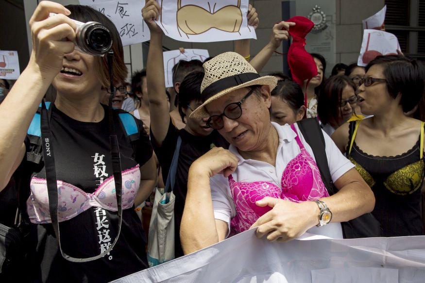 Protesters wear bras over their shirts during a demonstration in support of Hong Kong female protester Ng Lai-ying, outside the police headquarters in Hong Kong, China August 2, 2015. Ng was sentenced to three and a half months in jail for using her breast to bump against police at an anti-parallel trading protest, local media reported. REUTERS/Tyrone Siu
