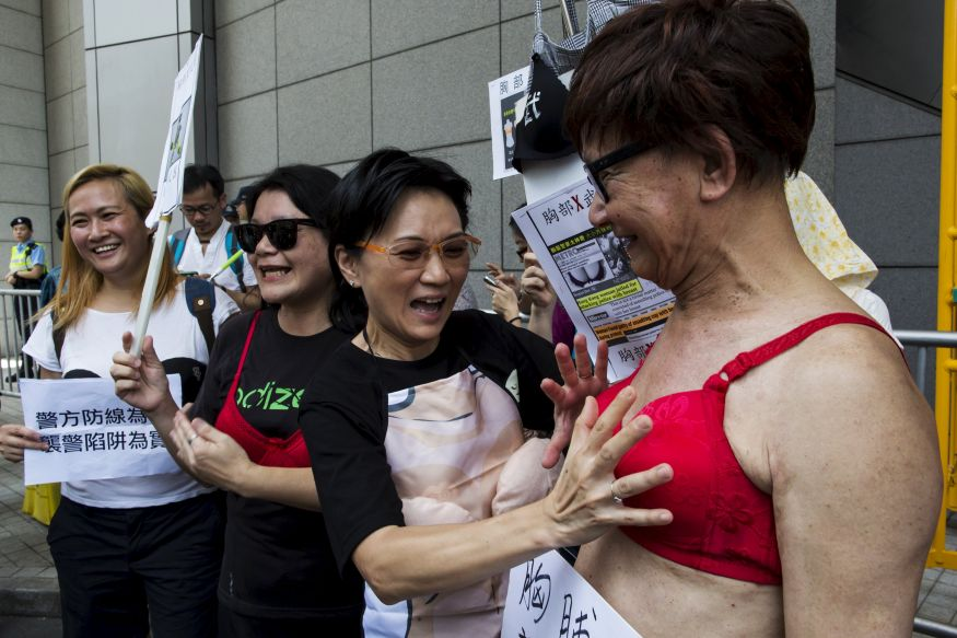 A protester (R) wears a bra during a demonstration in support of Hong Kong female protester Ng Lai-ying, outside the police headquarters in Hong Kong, China August 2, 2015. Ng was sentenced to three and a half months in jail for using her breast to bump against police at an anti-parallel trading protest, local media reported. REUTERS/Tyrone Siu