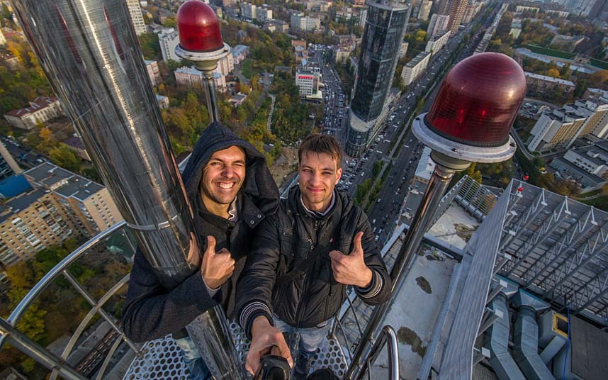 WITH PICS How's that for an extreme selfie? Urban climber Yaroslav Segeda, 22, went up a fire escape before scaling 80 metres to the top of this skyscraper. The engineer said he was only 'a little' scared in his trip to such a great height. Mr Segada went past the building's security guard, took the lift and then scrambled to the top to complete his mission in his home city Kyiv, Ukraine. SEE OUR COPY FOR DETAILS. Pictured: Urban climber Yaroslav Segeda (right) takes a selfie of himelf and friends at the top of a building in Kiev, Ukraine. Please byline: Yaroslav Seheda/Solent News  Yaroslav Seheda/Solent News & Photo Agency UK +44 (0) 2380 458800