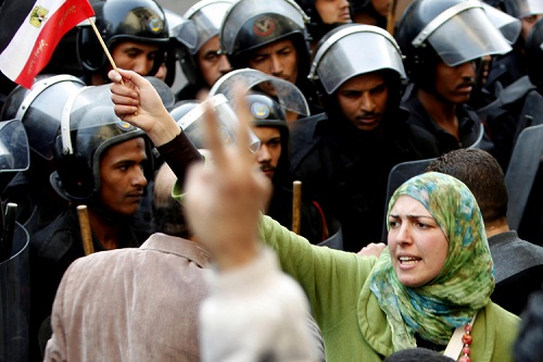 A woman holds an Egyptian flag in front of riot police during a protest in Cairo January 26, 2011. Thousands of Egyptians defied a ban on protests by returning to Egypt's streets on Wednesday and calling for President Hosni Mubarak to leave office, and some scuffled with police.  REUTERS/Asmaa Waguih (EGYPT - Tags: CIVIL UNREST POLITICS)
