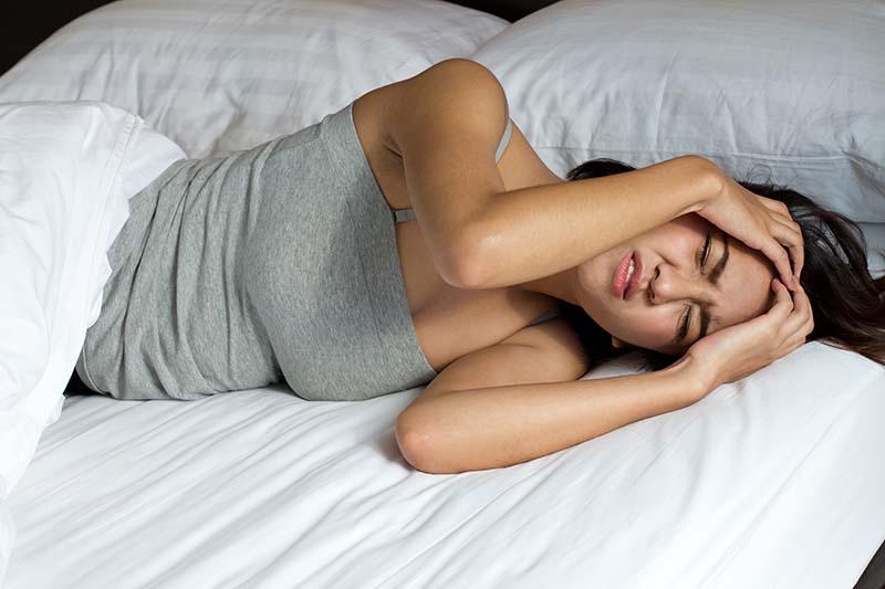 woman with headache migraine stress insomnia hangover