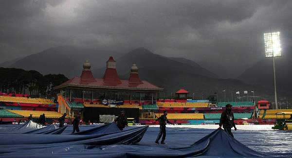Indian groundstaff cover the wicket as rain falls ahead of the World T20 cricket tournament qualifying match between Oman and The Netherlands at The Himachal Pradesh Cricket Association Stadium in Dharamsala on March 11, 2016.  / AFP / STR        (Photo credit should read STR/AFP/Getty Images)