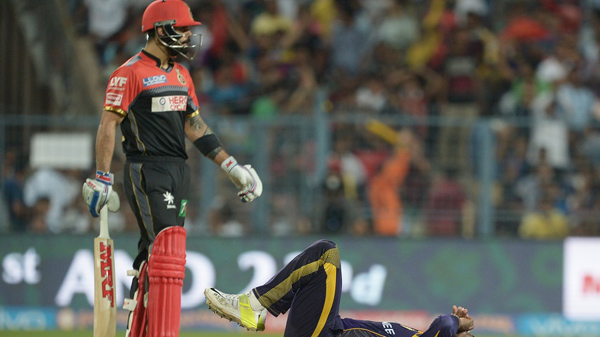 Royal Challengers Bangalore captain Virat Kohli (L) looks on as Kolkata Knight Riders Andre Russell falls during the 2016 Indian Premier League (IPL) Twenty20 cricket match between Kolkata Knight Riders and Royal Challengers Bangalore at the Eden Gardens Cricket Stadium in Kolkata on May 16, 2016.  ----IMAGE RESTRICTED TO EDITORIAL USE - STRICTLY NO COMMERCIAL USE----- / GETTYOUT' / AFP PHOTO / Dibyangshu SARKAR