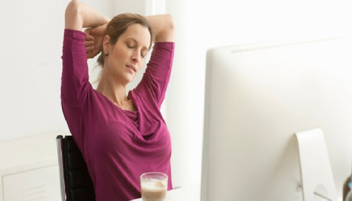 Woman stretching with eyes closed at desk